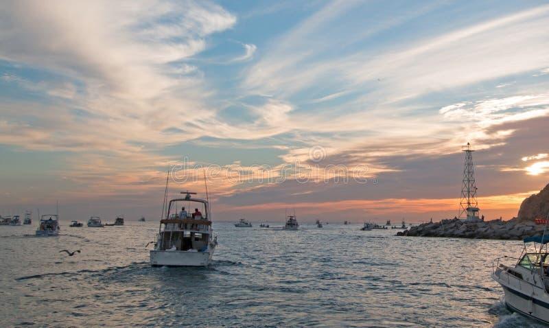 Den Fishermans soluppgångsikten av fiskebåtar som ut går för dagforntidsländerna, avslutar i Cabo San Lucas i Baja California Mex arkivbilder