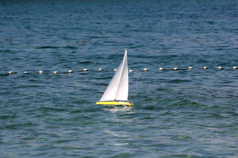 Den fjärrstyrda gula segelbåten med klart vitt seglar använt som barnleksaken i lokal fjärd på det rastlösa havet som omges med royaltyfria foton