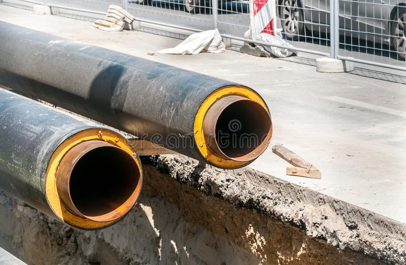 Den fjärrvärme isolerade rörrörledningskadeståndet och rekonstruktion som är parallella med gatan med konstruktionsplatsen, beläg arkivbilder