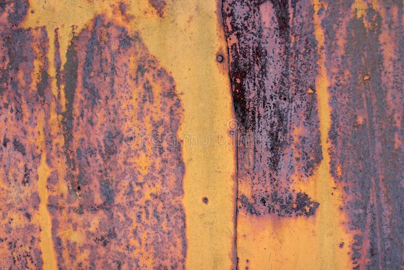 Den flagnande gula färgen med skrapat på yttersidan av den rostiga galvaniserade järnplattan Rostig guling målad metallvägg Rosti royaltyfri foto