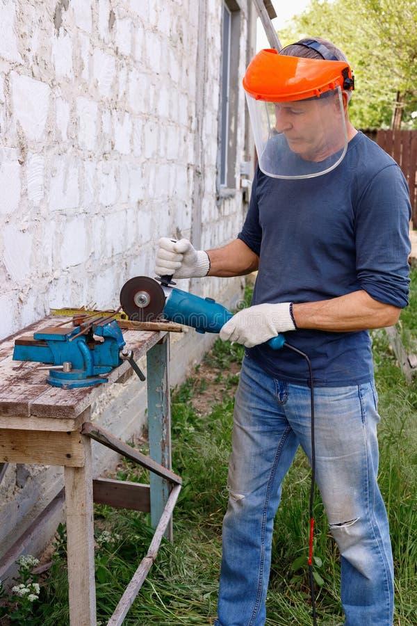Den flitiga effektiva allvarliga glade arbetaren gör reparationer med elektriska hjälpmedel bultar och plattång i trädgård av hus arkivbilder