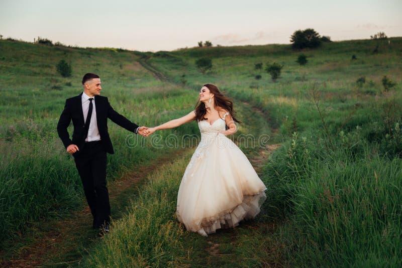 Den flotta bruden lyfter hennes klär upp, medan gå med brudgummen royaltyfria bilder