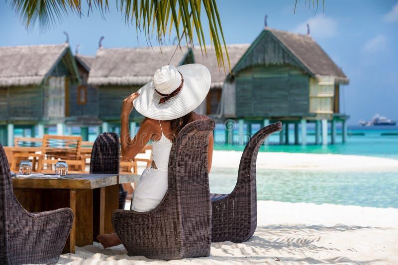 Den flotta kvinnan sitter på en lunchtabellaktivering på en strand i Maldiverna arkivfoton
