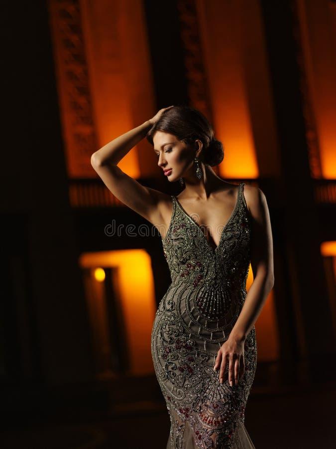 Den flotta och charmiga välklädda unga kvinnan i en smart afton dekorerade högt den dyra klänningen poserar i stadsgatan arkivfoto