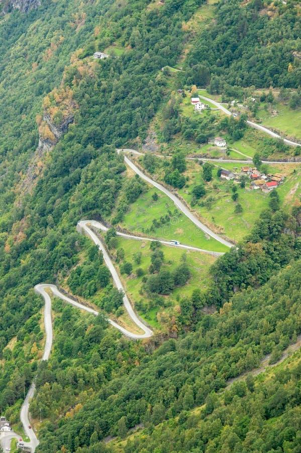 Den flyg- åtsittande sikten av en slingrig väg för sicksack som upp går ett stup nära Geiranger, Norge med något, trafikerar royaltyfri fotografi