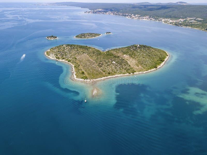 Den flyg- sikten av ön i formen av en hjärta, Kroatien, ön av vänner, Otok Galesnnjak, holme, vaggar Också kallad otokza Za arkivbild
