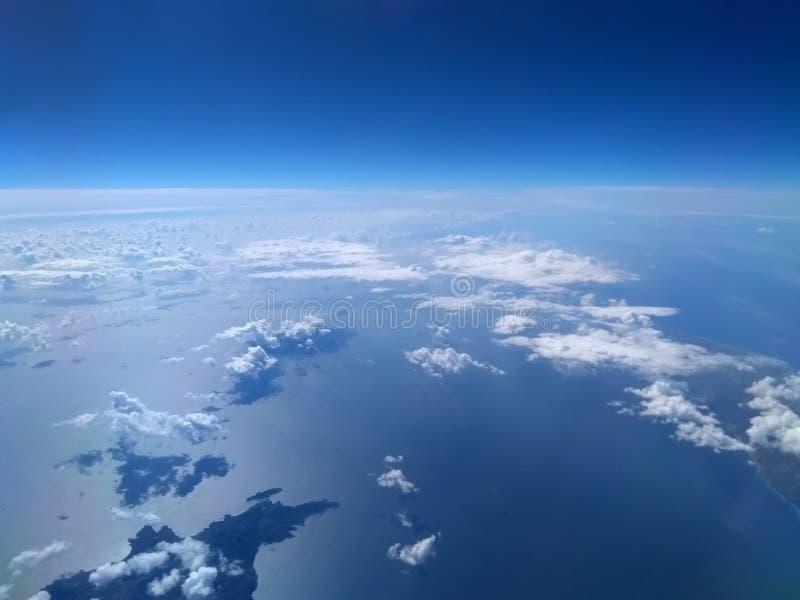 Den flyg- sikten av det ljus blå havet och himmel med vit fördunklar rollbesättningskuggor royaltyfri bild