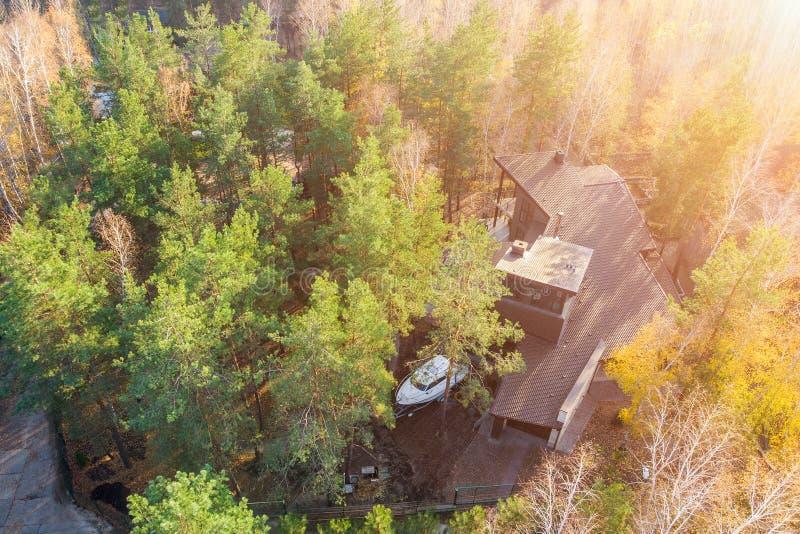 Den flyg- sikten av det stora moderna luxuty stugahuset mellan sörjer och björkträd i skog med fartyget på släpet som parkeras på arkivfoto