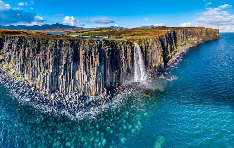 Den flyg- sikten av den dramatiska kustlinjen på klipporna vid Staffin med den berömda kilten vaggar vattenfallet - ön av Skye - arkivfoto