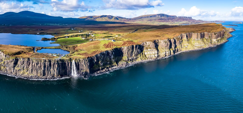 Den flyg- sikten av den dramatiska kustlinjen på klipporna vid Staffin med den berömda kilten vaggar vattenfallet - ön av Skye - royaltyfria foton