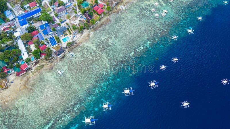 Den flyg- sikten av filippinska fartyg som ?verst sv?var av klart bl?tt vatten, Moalboal ?r ett djupt rent bl?tt hav och har m?ng royaltyfria bilder
