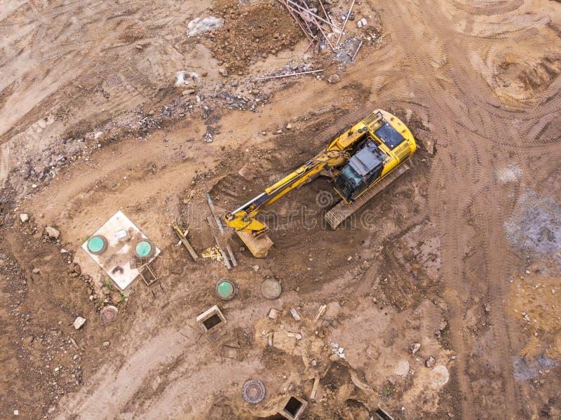 Den flyg- sikten av den gula grävskopan som gör earthmoving, arbetar royaltyfria foton