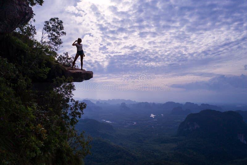Den flyg- sikten av kvinnan på kanten av vaggar på bergsiktspunkten royaltyfri foto