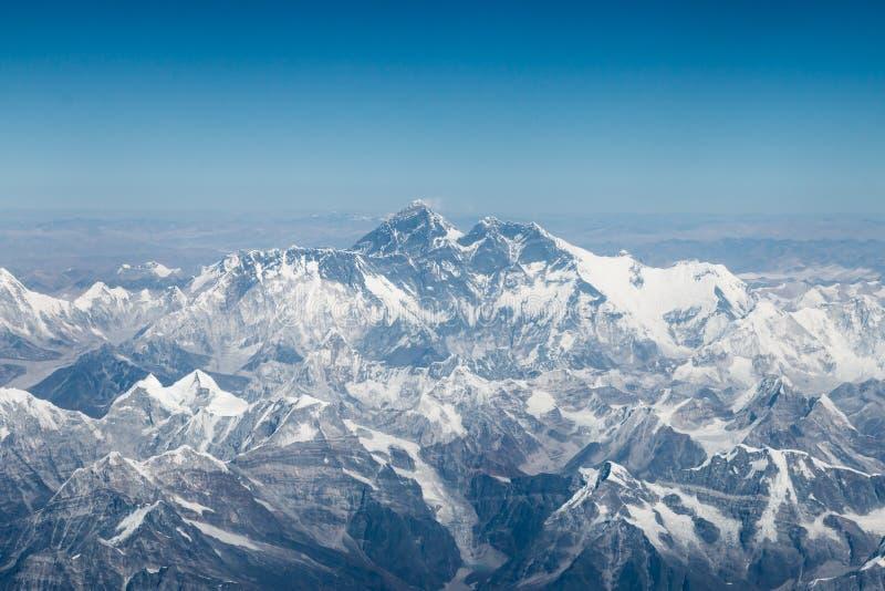Den flyg- sikten av Mount Everest och omgeende berg och snö täckte landskap, på flyget från Tibet till Nepal royaltyfria bilder