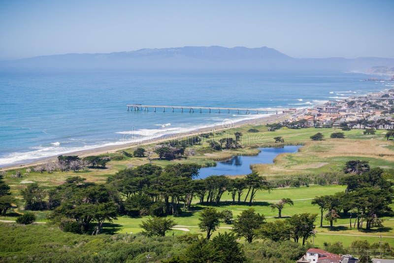 Den flyg- sikten av Pacifica Municipal Pier och kors parkerar golfbanan som sett uppifrån av Mori Point, Marin County i royaltyfri foto
