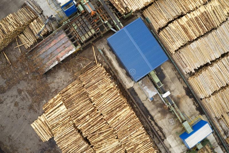 Den flyg- sikten av sågverket och den högg av trädträjournalen staplar i rad med maskineri royaltyfri bild