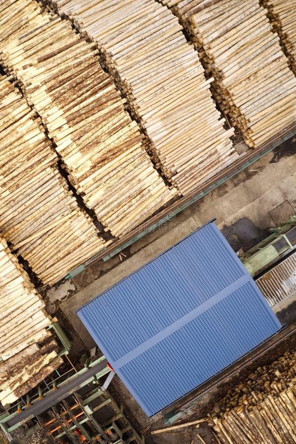 Den flyg- sikten av sågverket och den högg av trädträjournalen staplar i rad med maskineri arkivbild