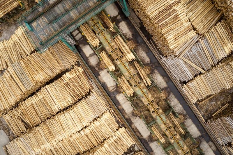 Den flyg- sikten av sågverket och den högg av trädträjournalen staplar i rad med maskineri arkivfoto