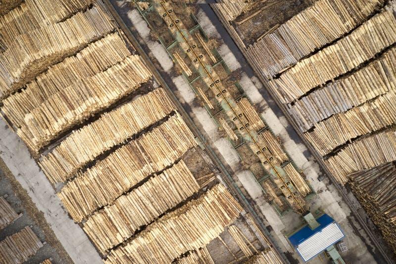 Den flyg- sikten av sågverket och den högg av trädträjournalen staplar i rad med maskineri arkivbilder