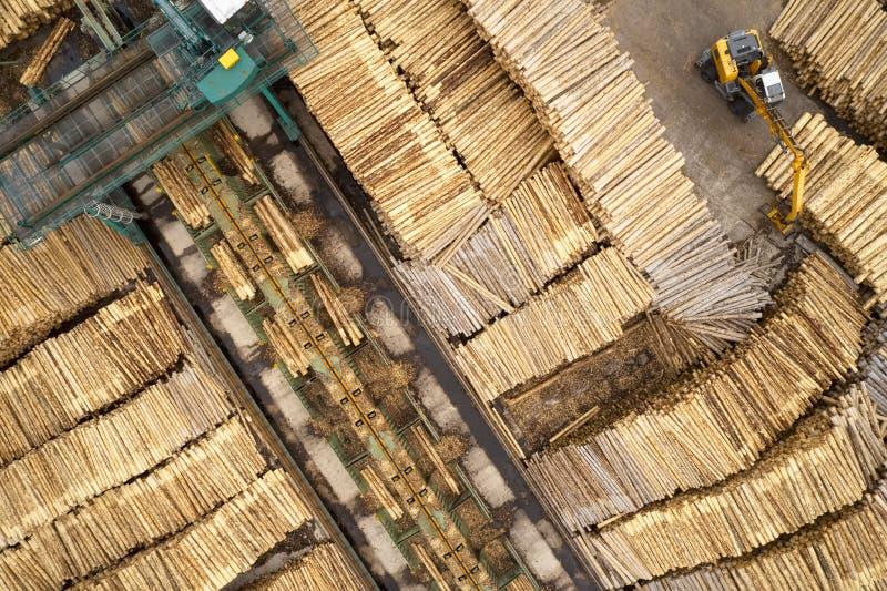 Den flyg- sikten av sågverket och den högg av trädträjournalen staplar i rad med maskineri arkivfoton