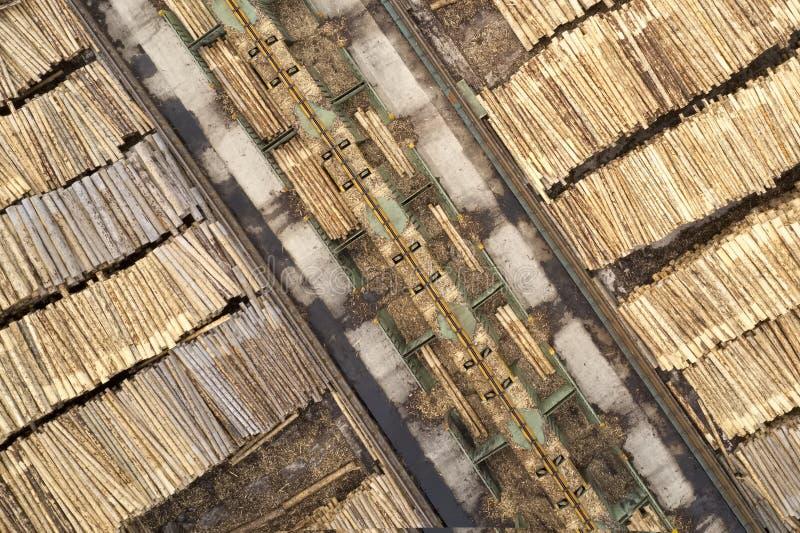 Den flyg- sikten av sågverket och den högg av trädträjournalen staplar i rad med maskineri royaltyfri fotografi