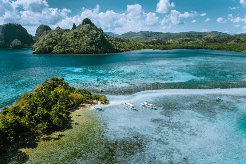 Den flyg- sikten av den turkosvatten och sandbaren på den tropiska Vigan ormön, turist- dragningar, turnerar flottan för turEl Ni arkivfoton