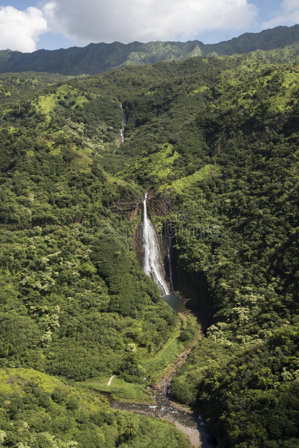 Den flyg- sikten av vattenfallet Manawaiopuna faller, använt i Jurassic parkerar, Kauai, Hawaii royaltyfria foton