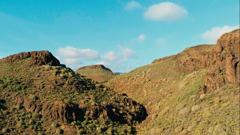 Den flyg- surrbilden av härliga bedöva landskapklippor vaggar maxima och dalar med en curvy väg på en solig dag royaltyfri foto