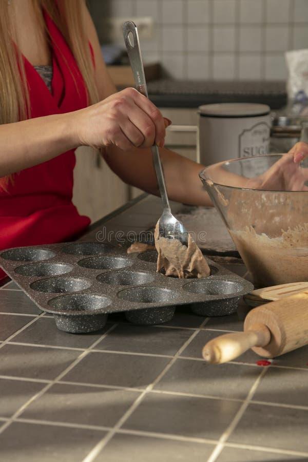 Den fokuserade flickan i en juldräkt bakar muffin, slut upp på handen fotografering för bildbyråer