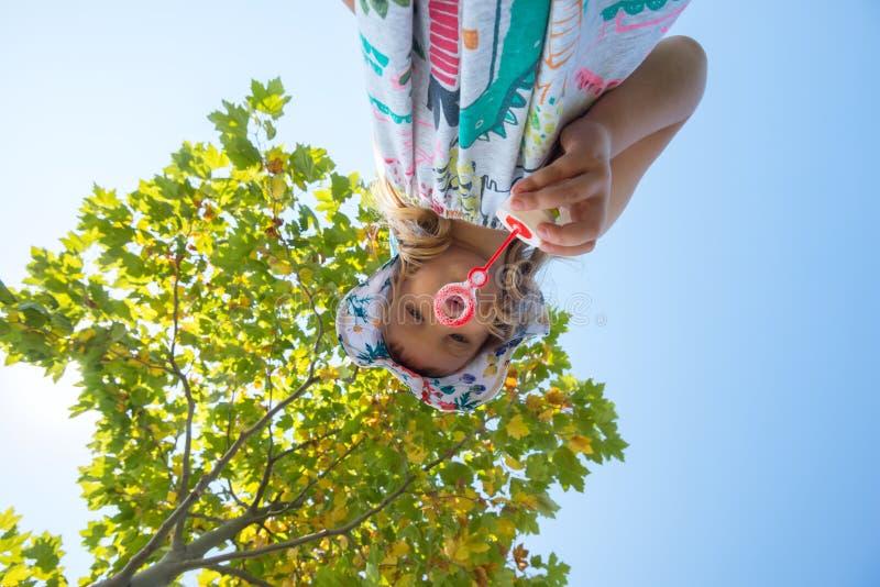 Den fokuserade lilla flickan blåser såpbubblor arkivfoton