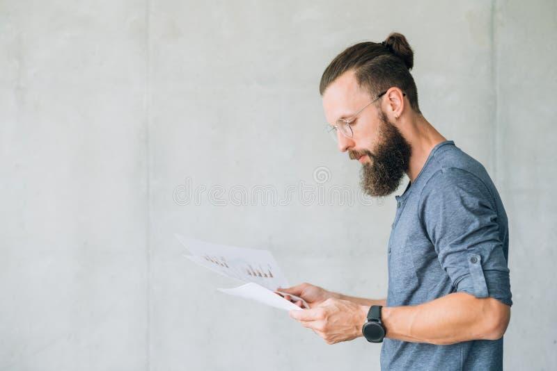 Den fokuserade mannen läste för informationsrapport om dokument data royaltyfria foton