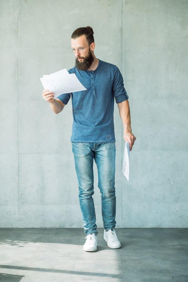 Den fokuserade mannen läste för informationsrapport om dokument data arkivfoto