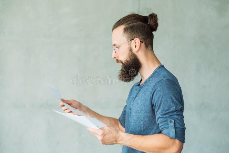 Den fokuserade mannen läste information om affärsdokument arkivbild