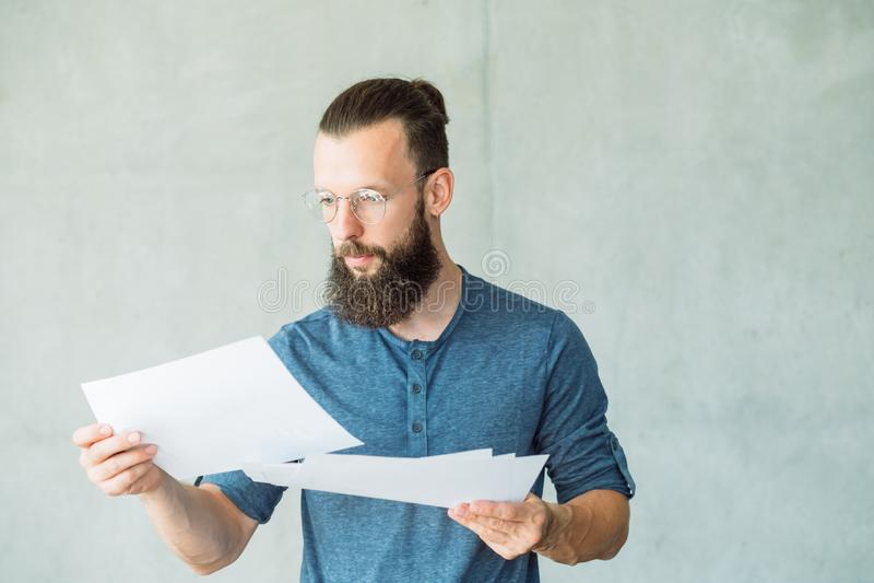 Den fokuserade mannen läste information om affärsdokument fotografering för bildbyråer