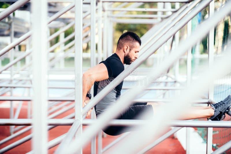 Den fokuserade muskulösa mannen som in utarbetar, parkerar, triceps och beväpnar genomkörare arkivbilder