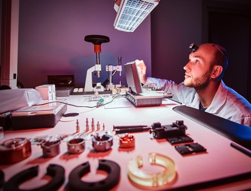 Den fokuserade urmakaren arbetar p? hans egen studio arkivbild