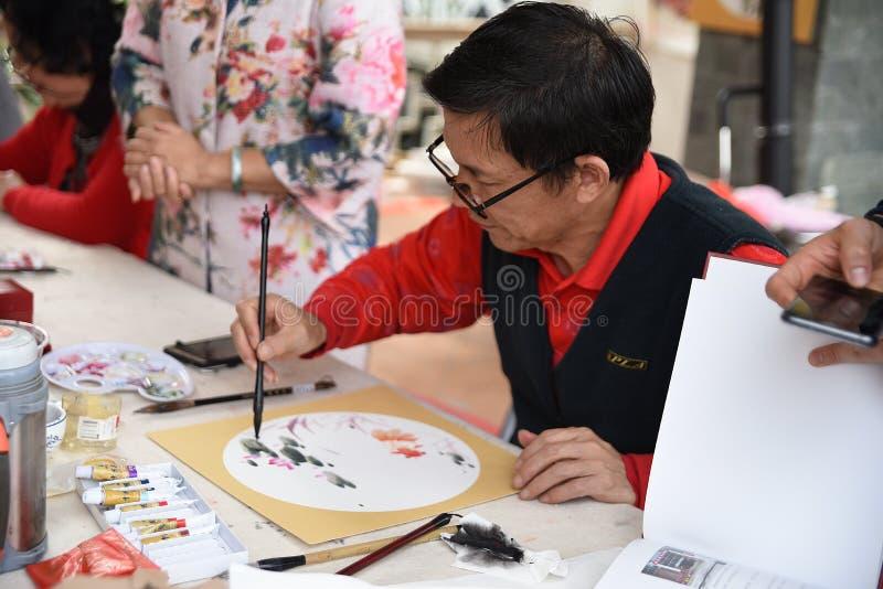 Den folk hantverkaren som gör kinesiska fans royaltyfria bilder