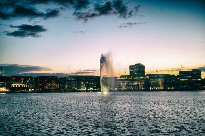 Den Fontaene Hamburg Alster Wohnhaeuser luxusen wellen himmel för natten för nachtabendvågen arkivbilder