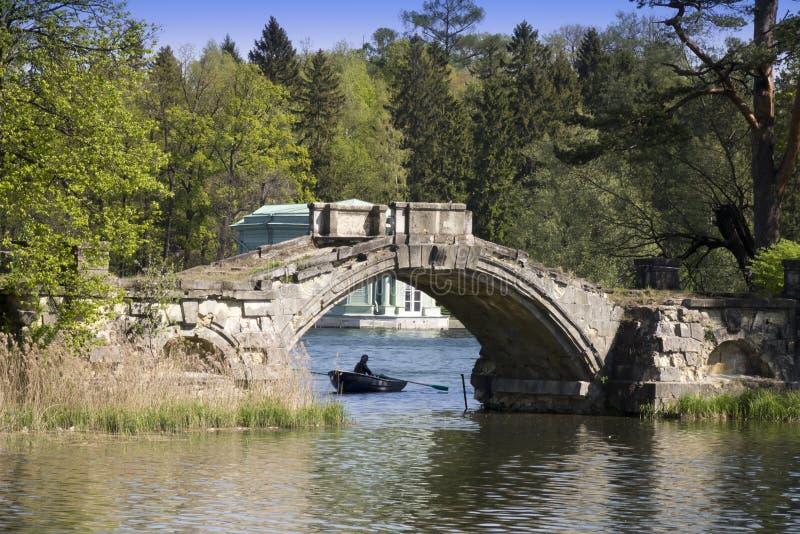 Den forntida förstörda bron i den tidigare slotten parkerar Gatchina petersburg Ryssland fotografering för bildbyråer