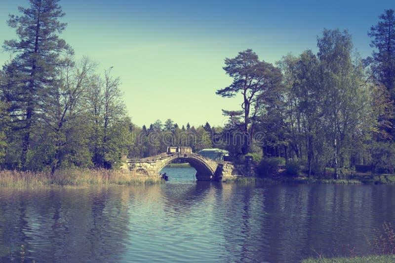 Den forntida förstörda bron i den tidigare slotten parkerar, retro effekt royaltyfri bild