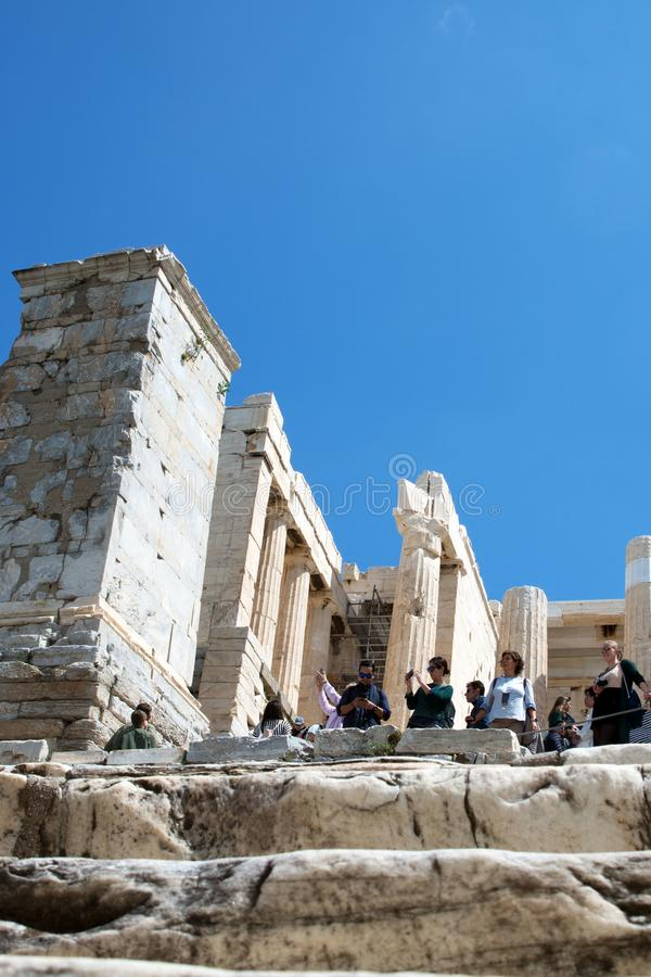 den forntida greken f?rd?rvar Akropol: Turister bland fördärvar av akropolen tar bilder av sikten och ser huvudstaden av arkivfoto