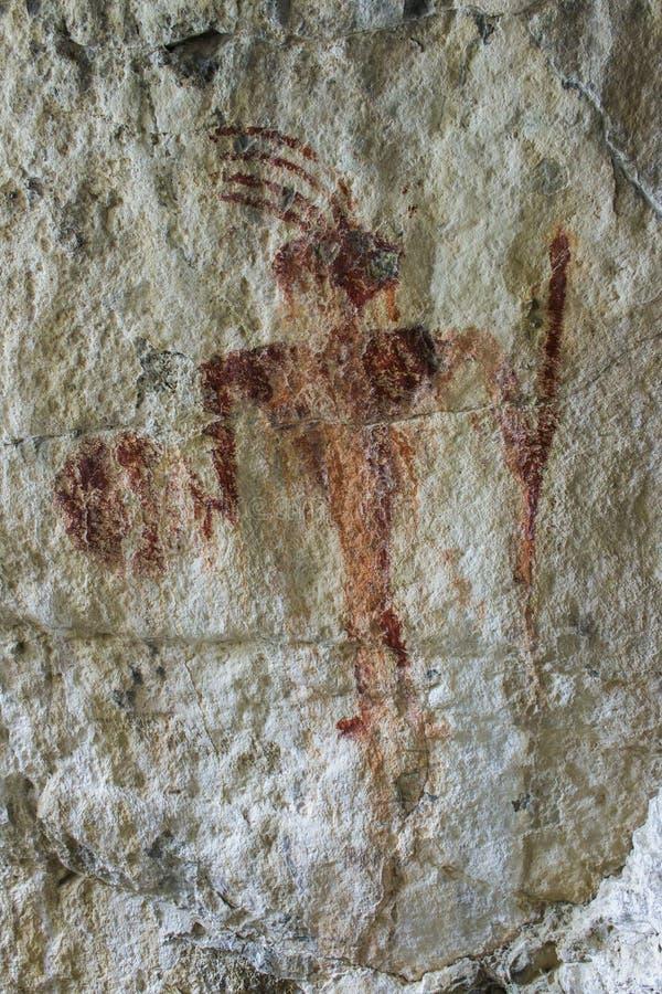 Den forntida pictographen för den röda mannen vaggar målning arkivbilder