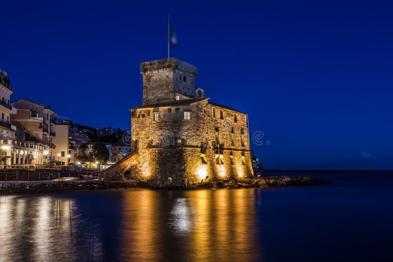 Den forntida slotten på havet vid natten, Rapallo, Genoa Genova, Italien royaltyfri bild