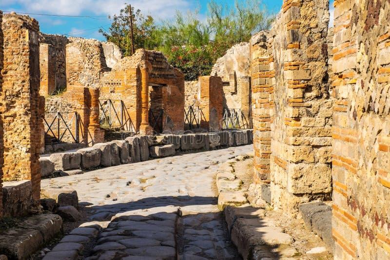 Den forntida stenlade gatan återställs i mitt av romaren fördärvar i Pompeii, Italien royaltyfria foton