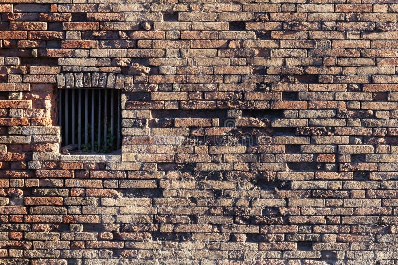Den forntida tegelstenväggen, fönster låste med metallstänger royaltyfri fotografi
