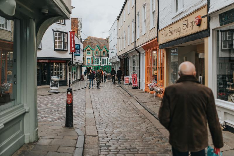 Den fot- promenera cobblestoned gatan, med shoppar runt om den och traditionell arkitektur i byn av Canterbury, arkivbild