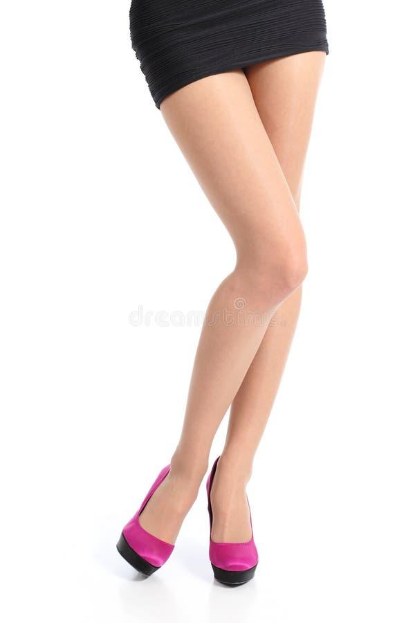 Den främre sikten av en kvinna lägger benen på ryggen med höga häl för fuchsian som poserar att stå royaltyfri fotografi