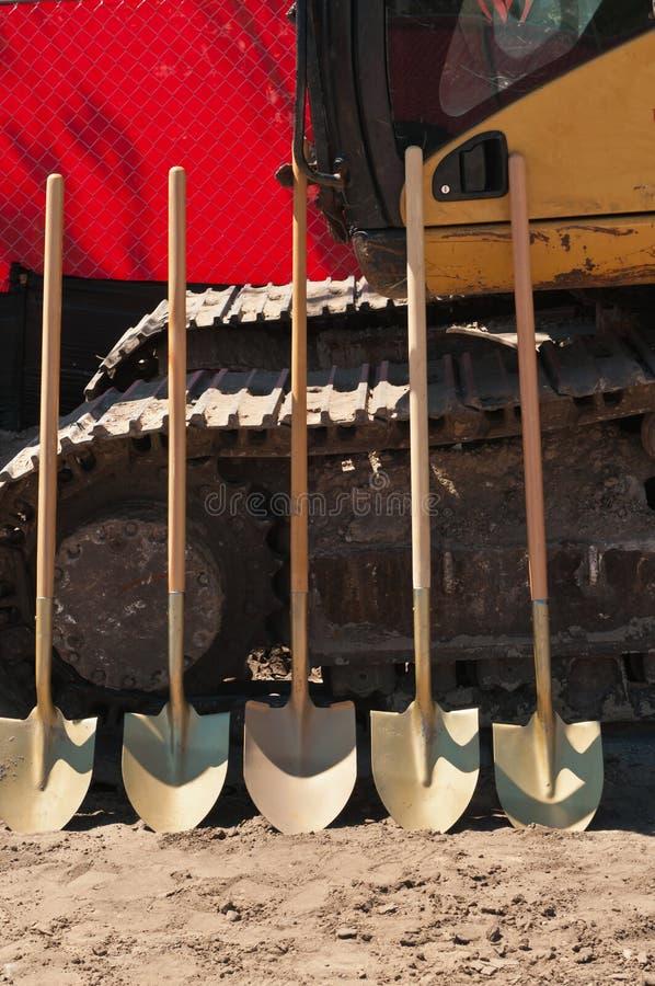 Den främre sikten av fem skyfflar som ska används i en jordbrytande ceremoni för ett tropiskt som är offentlig parkerar arkivfoton