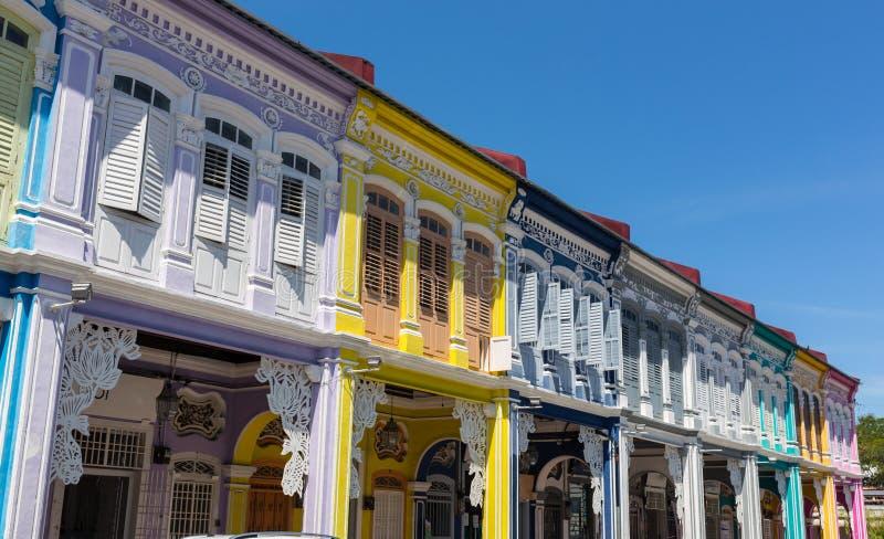 Den främre sikten av traditionell tappning Singapore shoppar huset eller shophouse med antika röda, blåa och gula träslutare in arkivfoton