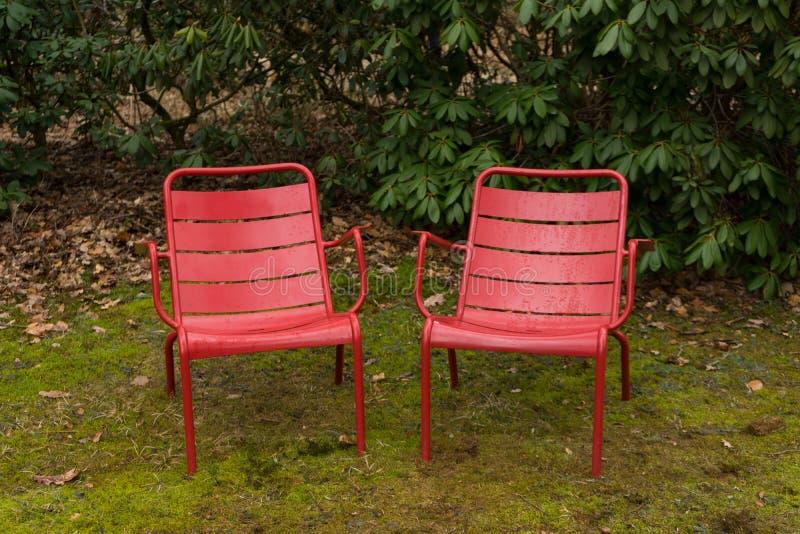 Den främre sikten av två röda stolar inom parkerar arkivfoto